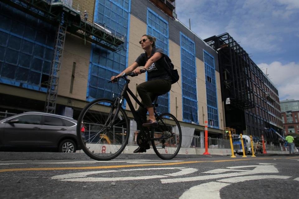 A cyclist on the new protected bike lane on Causeway Street passed new construction.